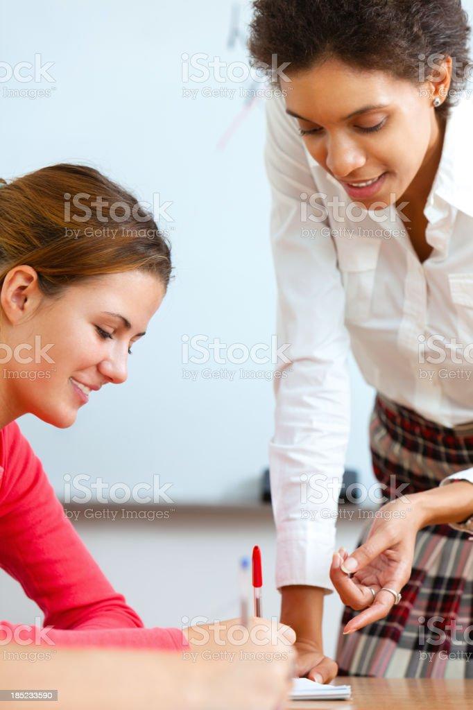 Teacher helping teenage student royalty-free stock photo