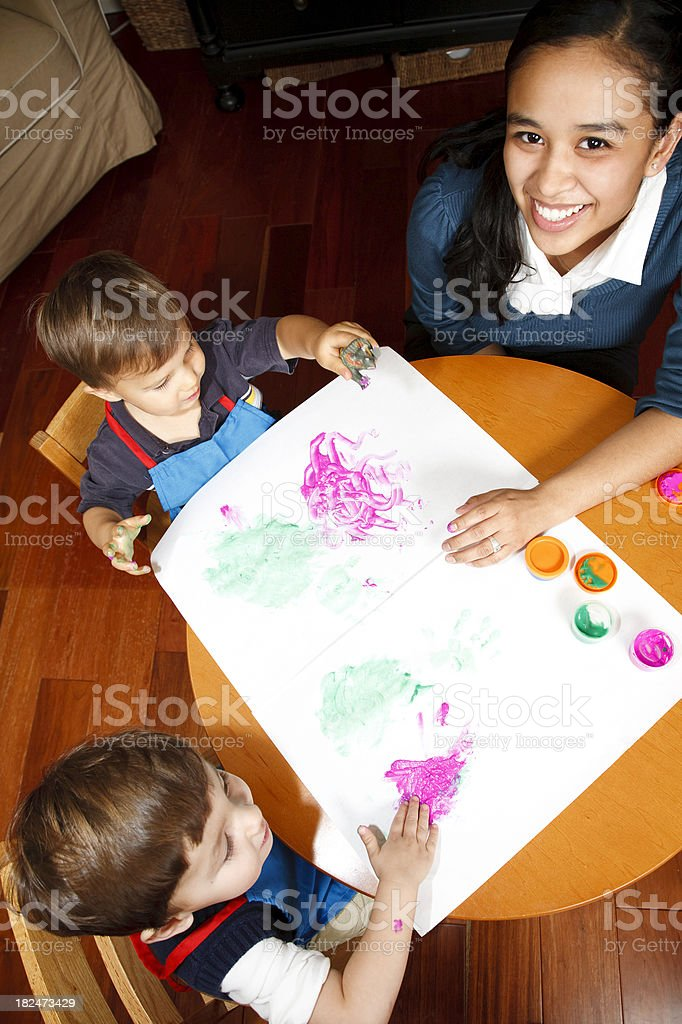 Teacher Helping Toddler Boys with Finger Painting royalty-free stock photo