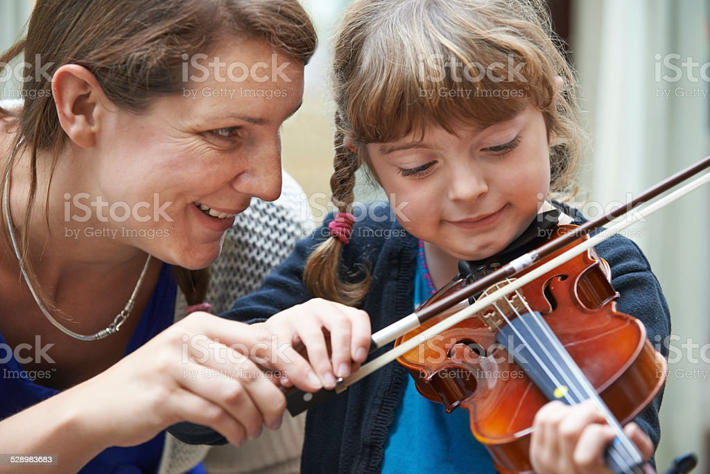 Teacher Helping Young Female Pupil In Violin Lesson stock photo