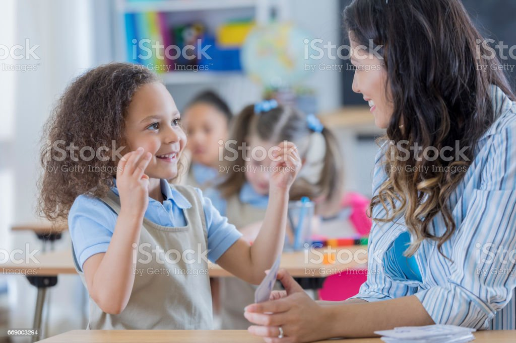 Teacher helps young student with math stock photo