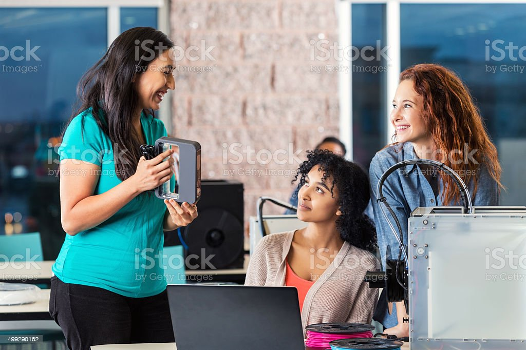 Teacher holding 3D scanner next to 3D printers in classroom stock photo
