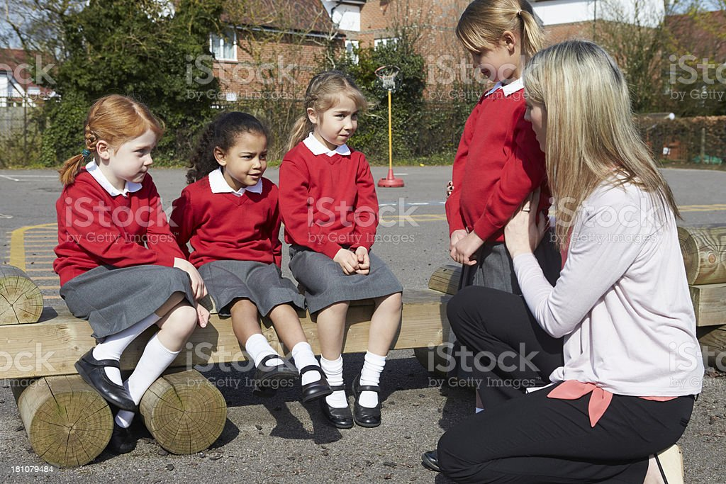 Teacher holding a little girl while talking to three others stock photo