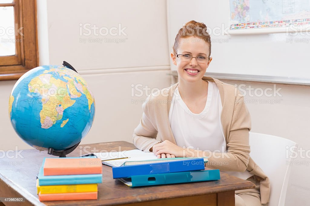 Teacher in classroom with globe stock photo