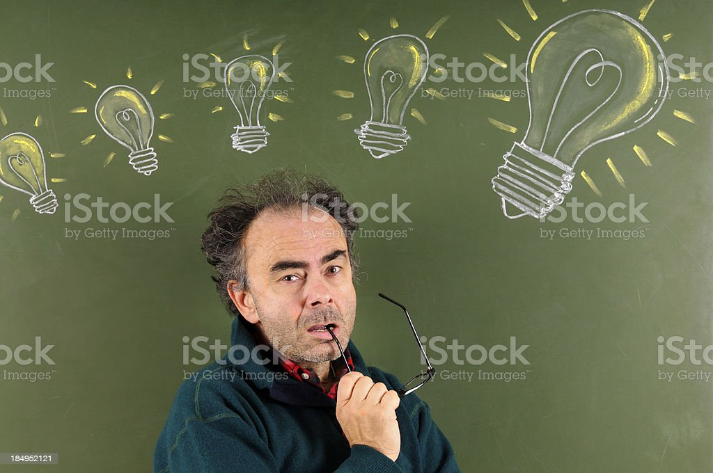 Teacher in Front Of Blackboard W Sketched Light Bulbs royalty-free stock photo