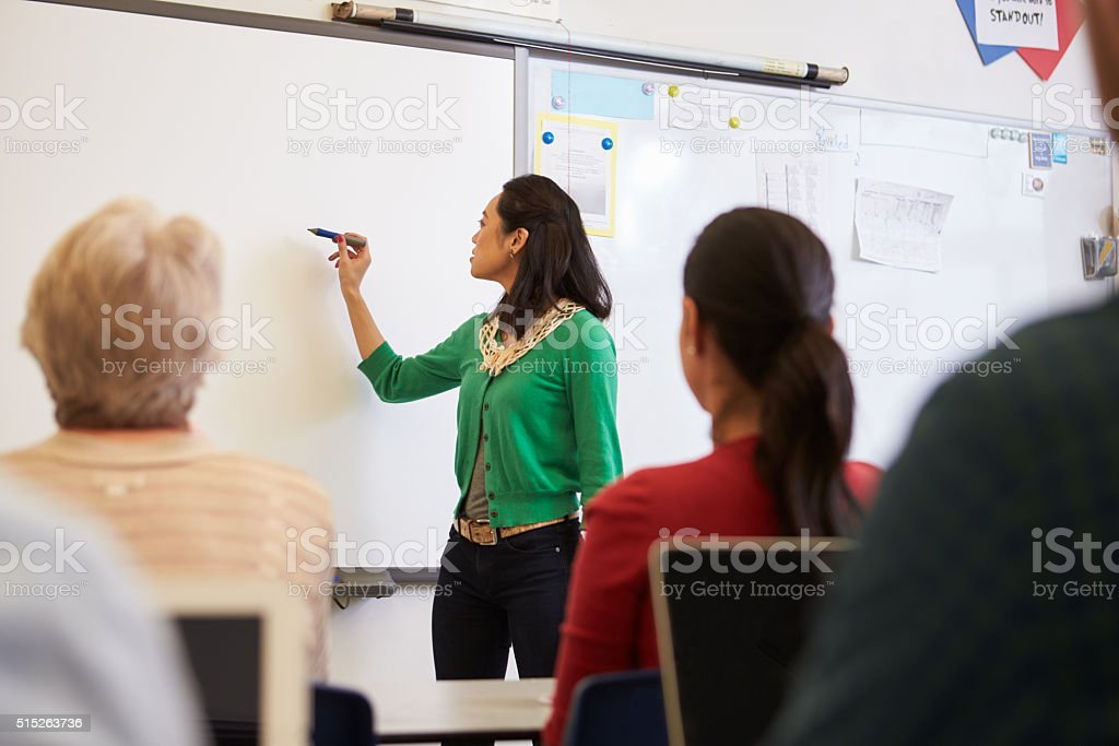 Teacher in front of students at an adult education class stock photo