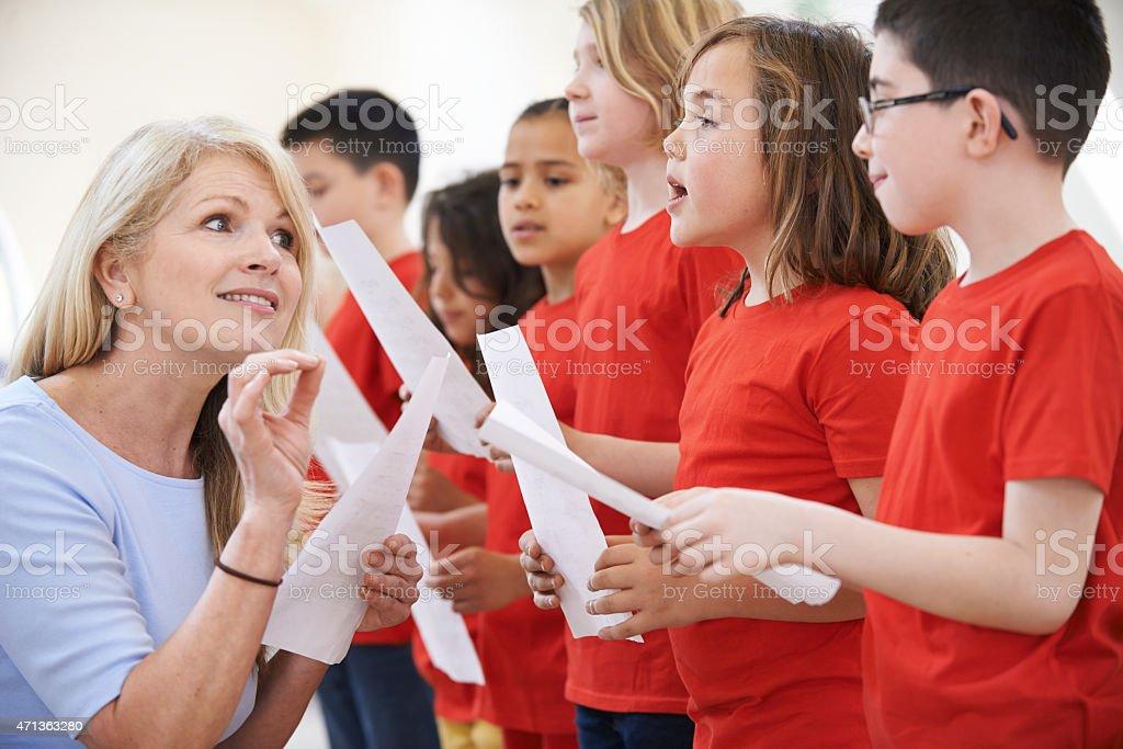 Teacher instructs a children's choir dressed in red stock photo