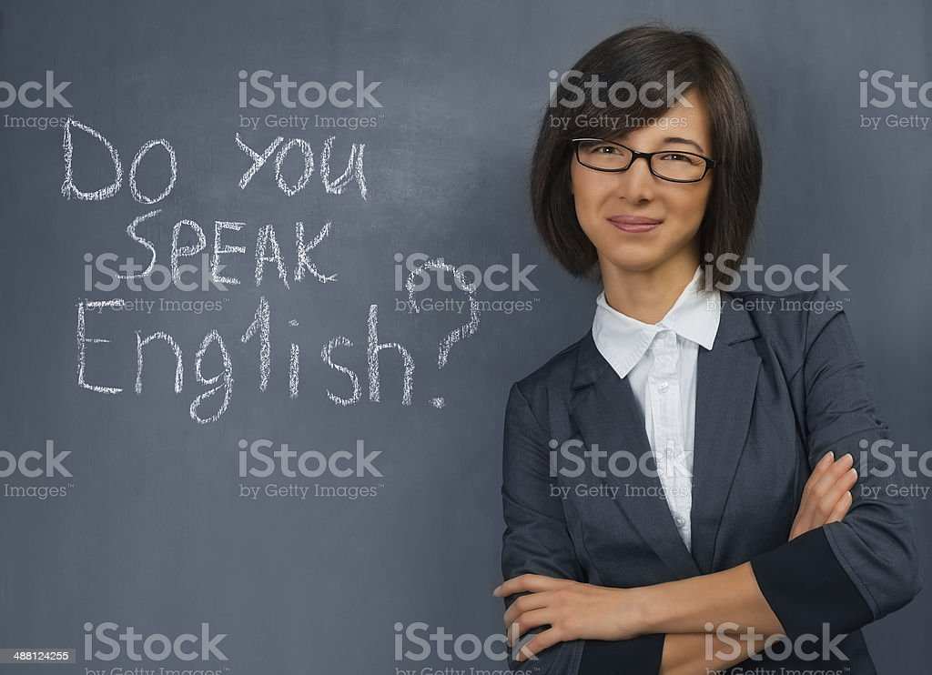 Teacher is standing near blackboard stock photo