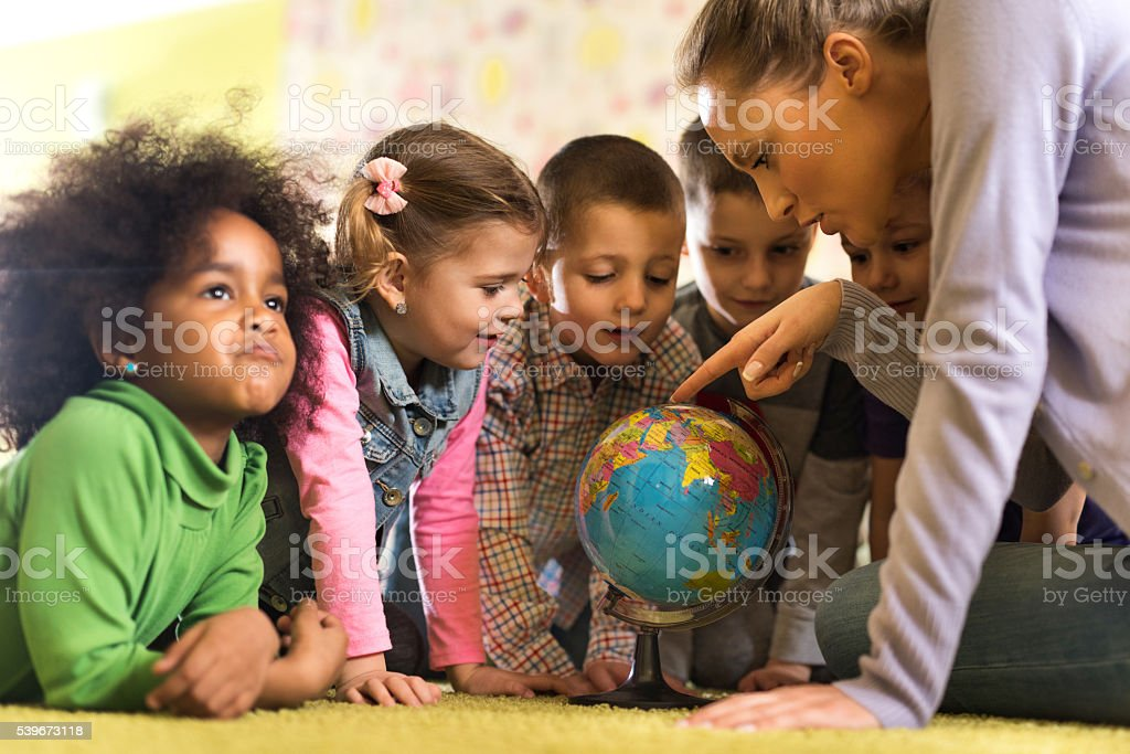 Teacher looking at world globe with group of preschoolers. stock photo