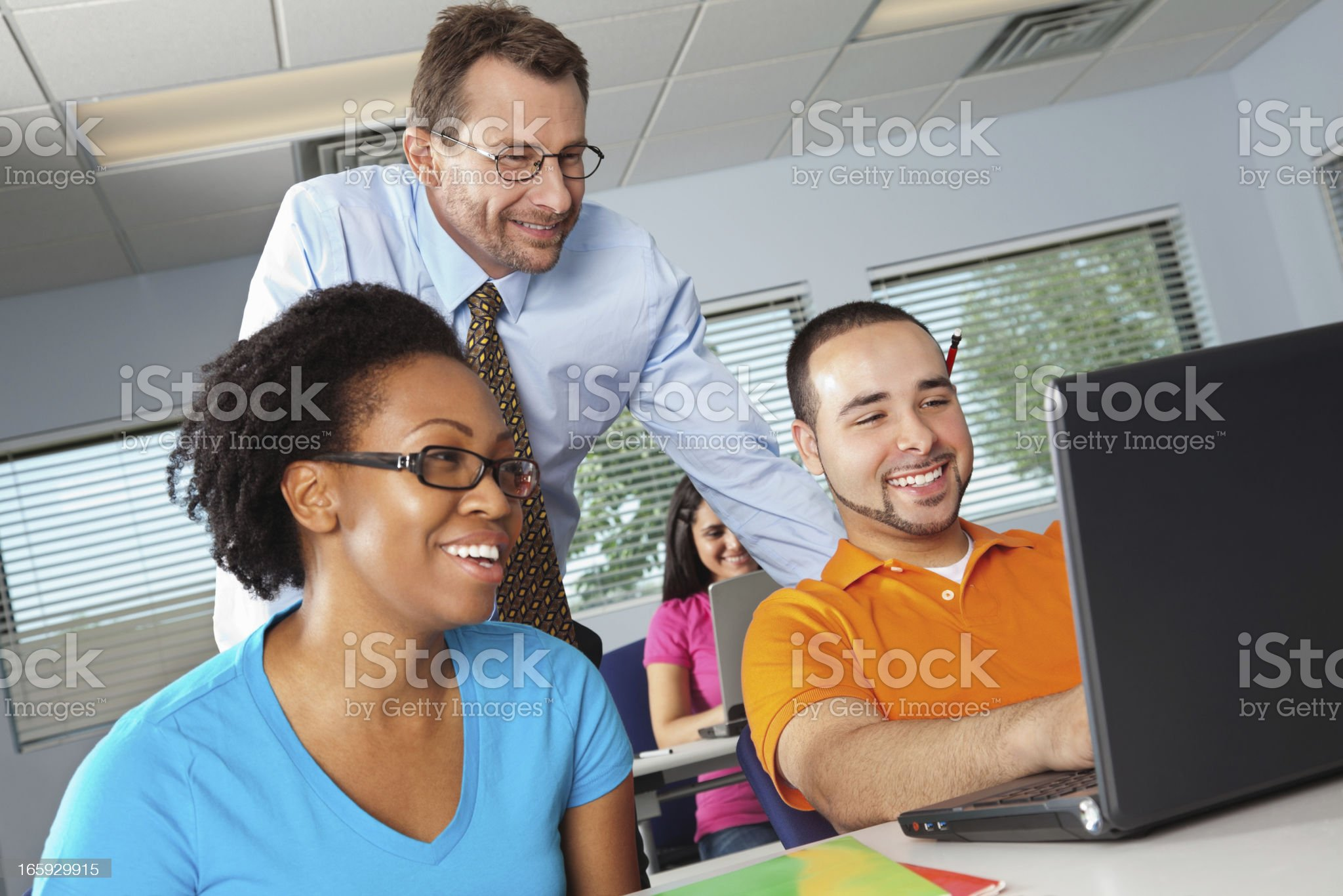 Teacher looking over his student's work in classroom royalty-free stock photo