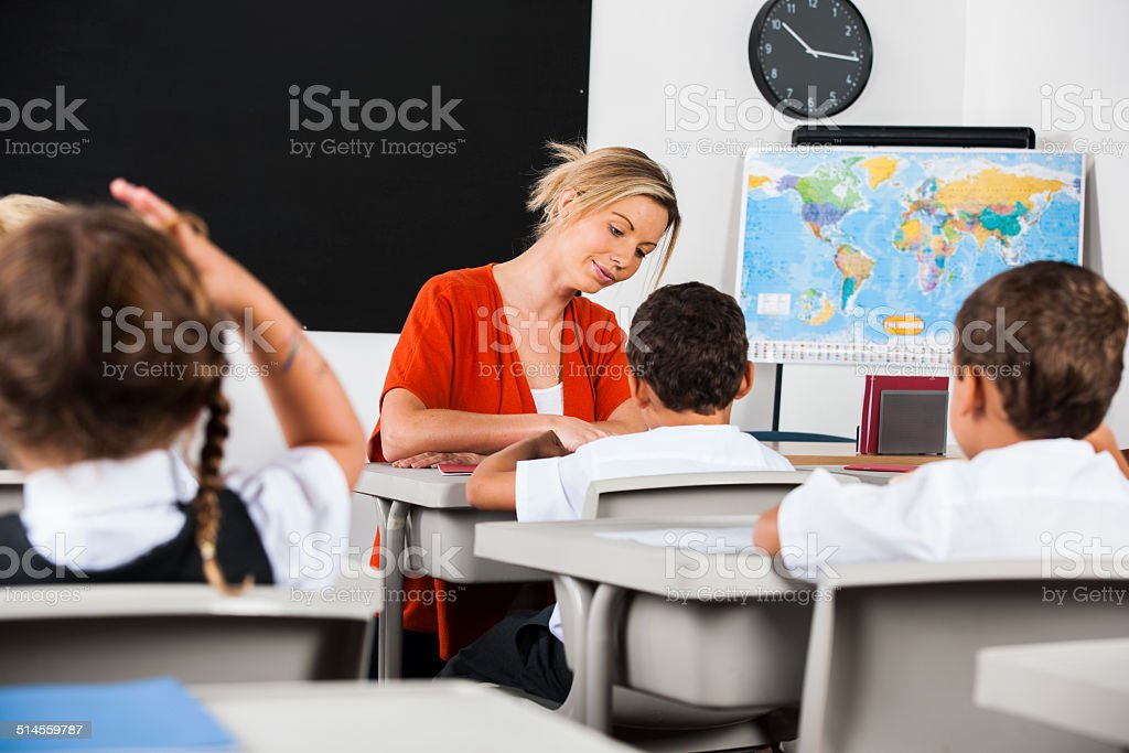 Teacher Marking/ Grading Schoolwork While Students Undertake Their Assignment stock photo