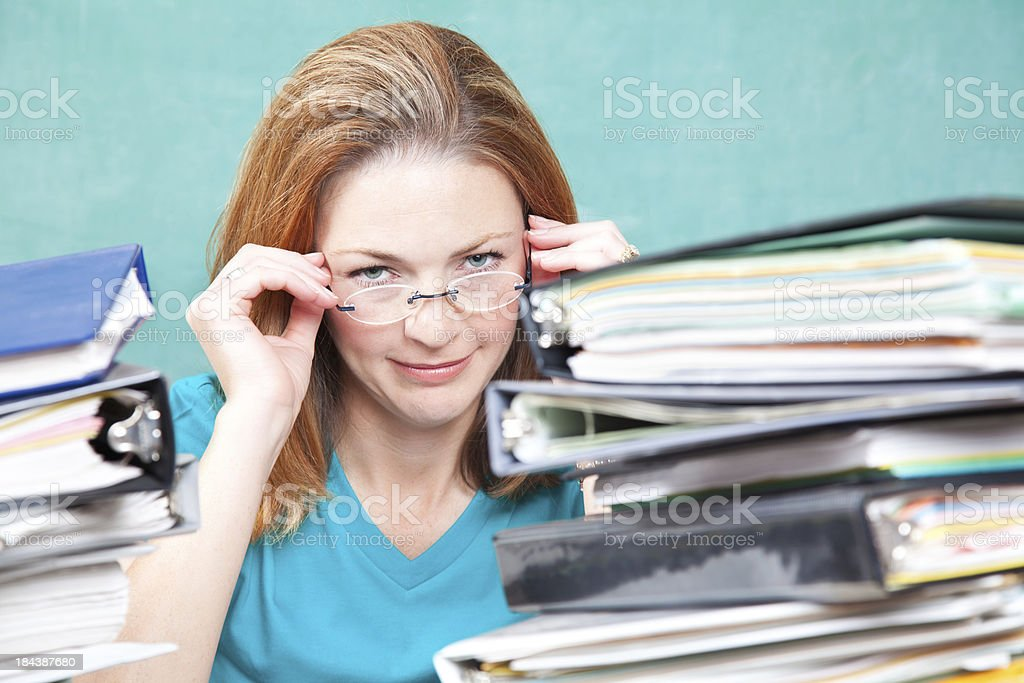 Teacher or Graduate Student Holding Glasses With Piles of Work royalty-free stock photo