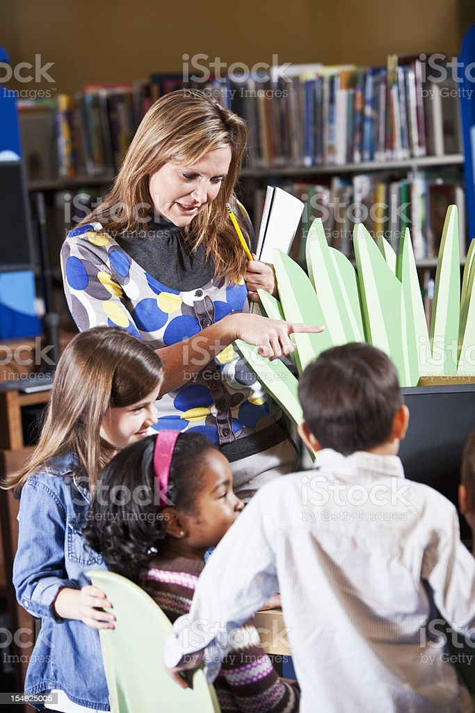Teacher or librarian helping multiracial children use computer stock photo