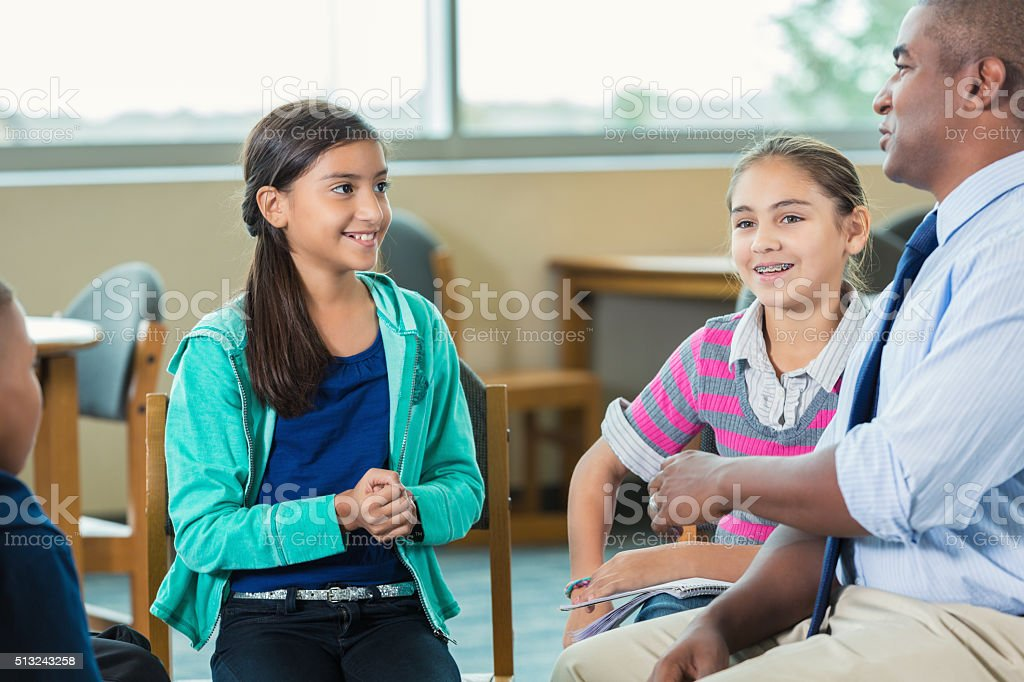 Teacher or school counselor leads diverse group of elementary students stock photo