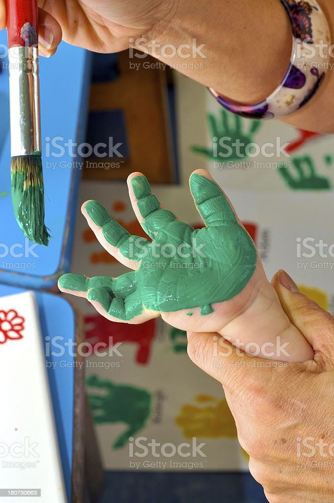 Teacher Painting Preschooler's Hand royalty-free stock photo