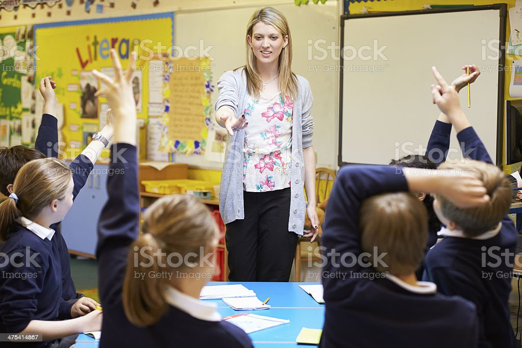 Teacher pointing to students with raised hands stock photo