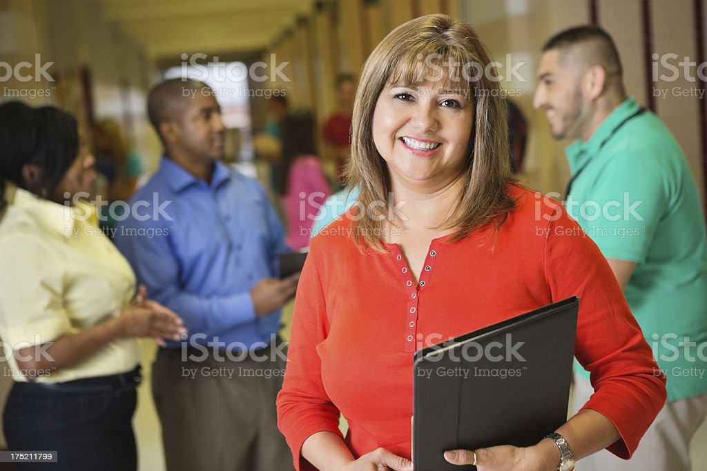 Teacher posing in high school hallway with other administrators stock photo