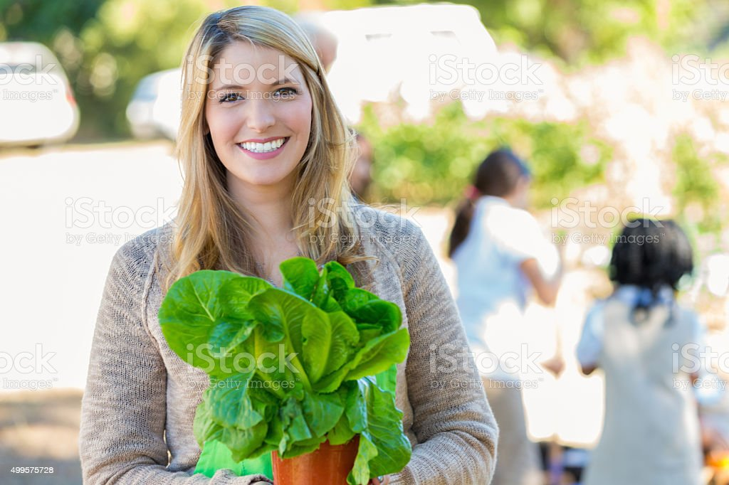 Teacher preparing to plant vegetables during outdoor science class stock photo