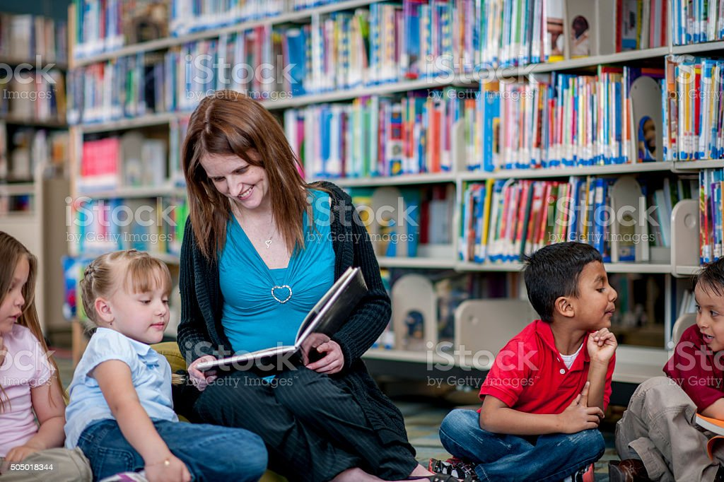 Teacher Reading a Book to Students stock photo
