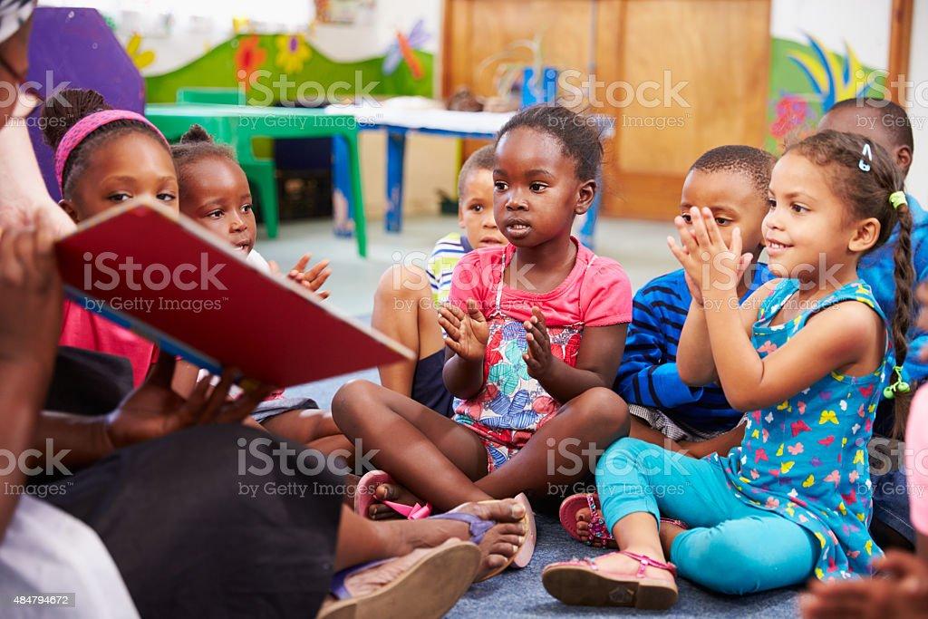 Teacher reading a book with a class of preschool children stock photo