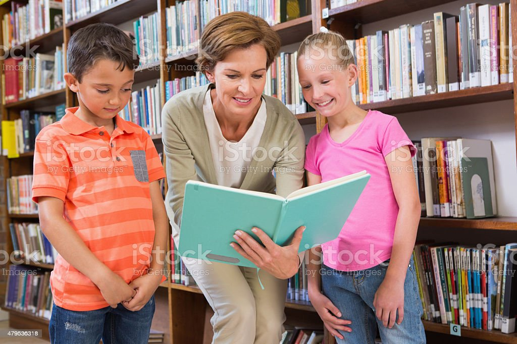 Teacher reading book with pupils at library stock photo