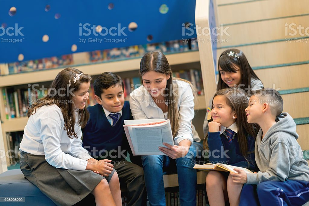 Teacher reading books to a group of students stock photo