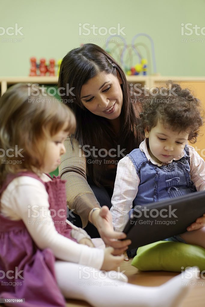 Teacher reading fairy tale to children at school stock photo