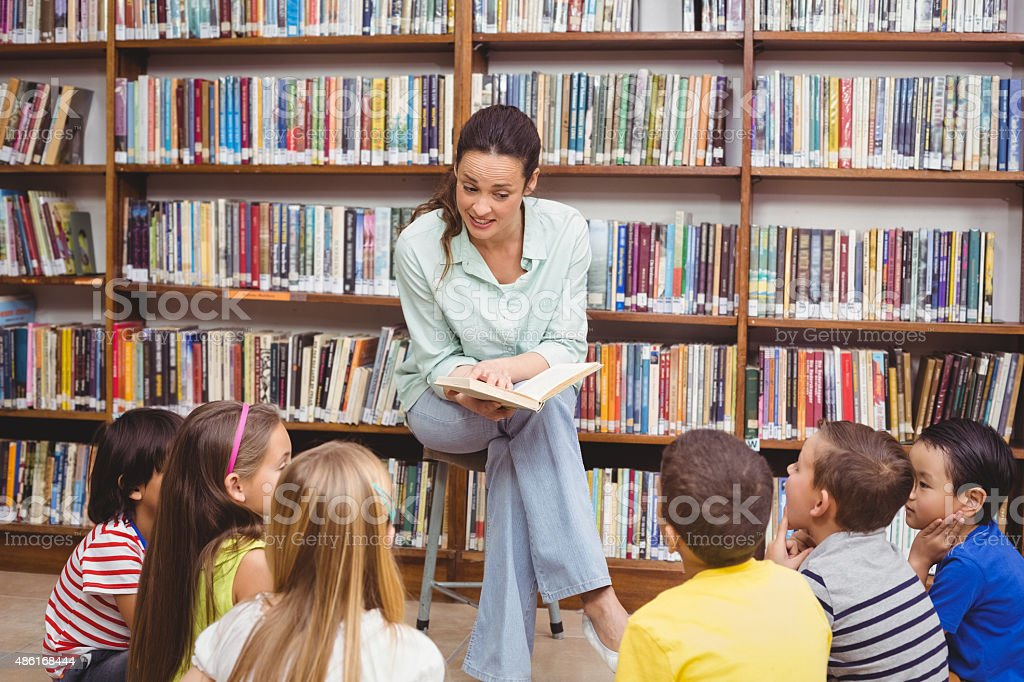 Teacher reading her pupils a story stock photo