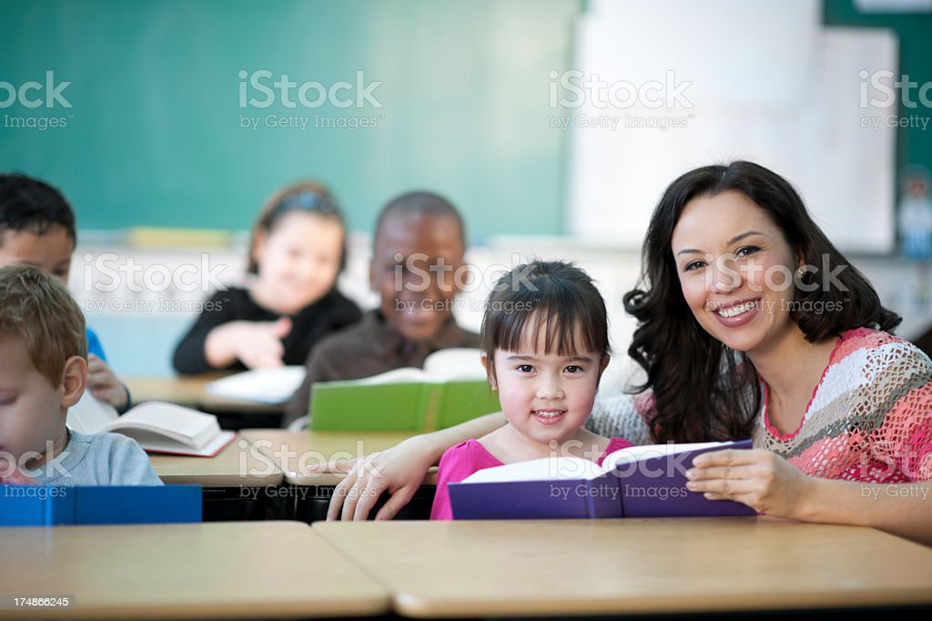 teacher reading with elementary students stock photo