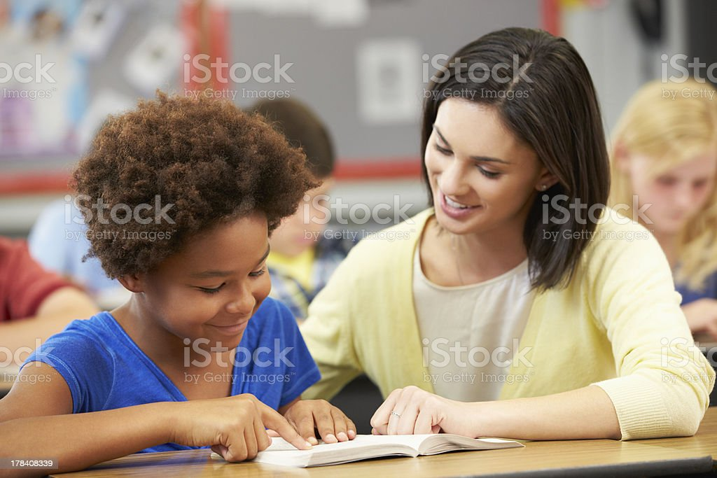 Teacher Reading With Female Pupil In Class stock photo