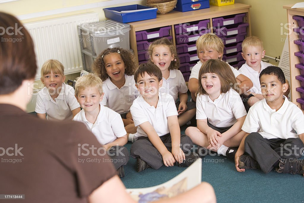 Teacher reads to schoolchildren in a primary class stock photo