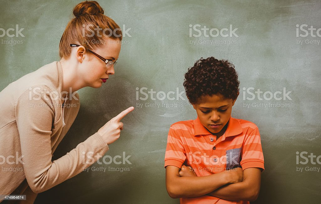 Teacher shouting at boy in classroom stock photo