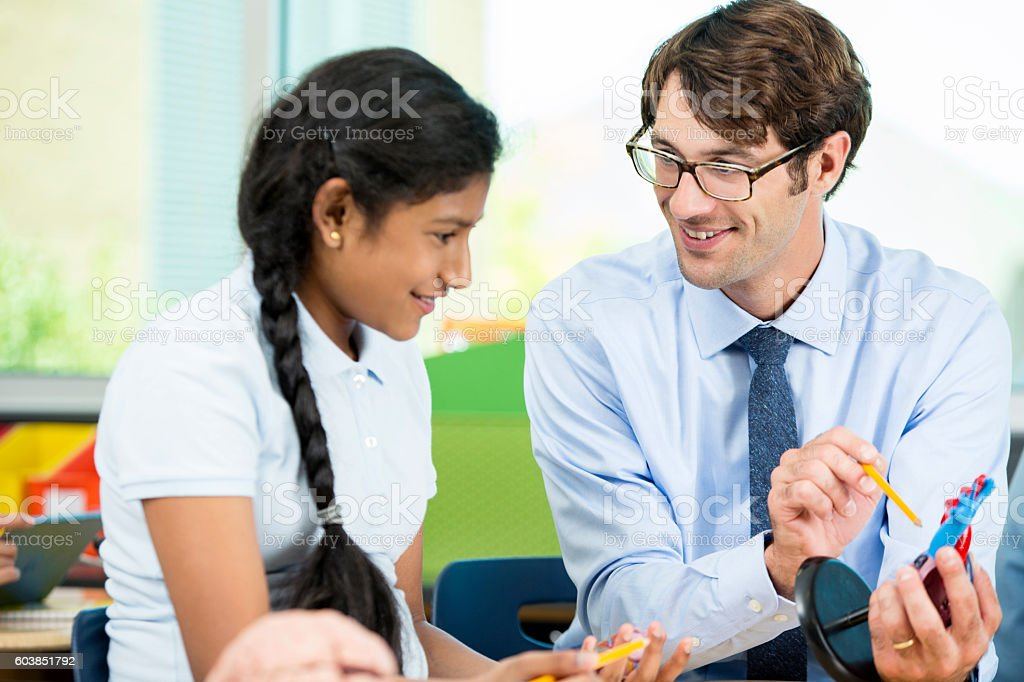 Teacher showing a heart model to student in science class stock photo