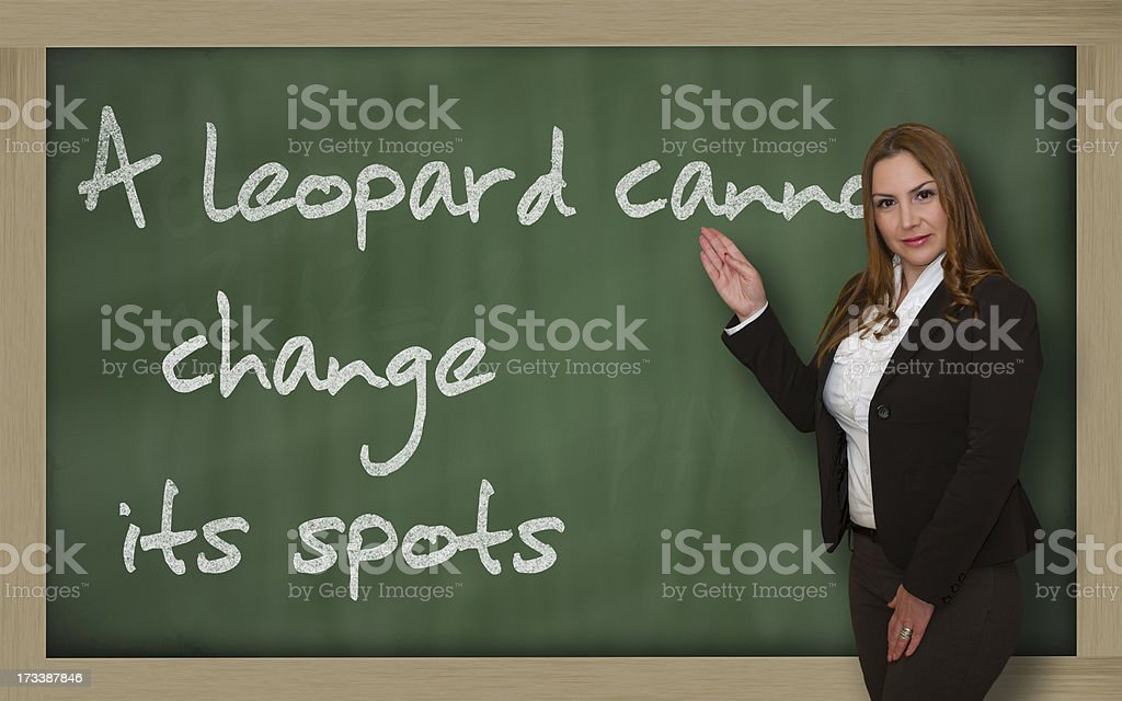 Teacher showing A leopard cannot change its spots on blackboard royalty-free stock photo