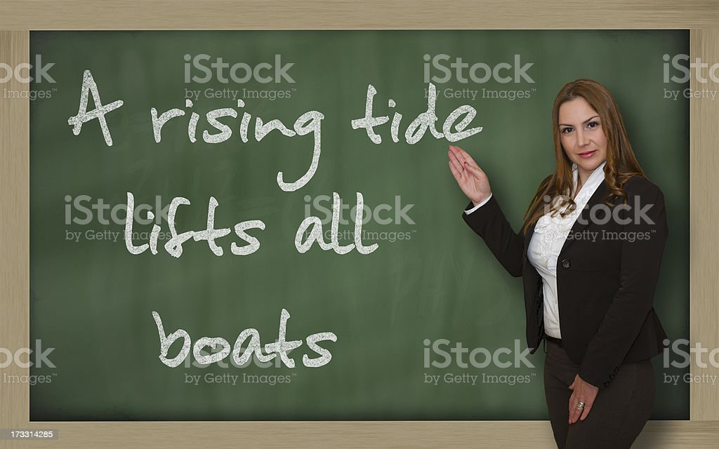 Teacher showing A rising tide lifts all boats on blackboard stock photo