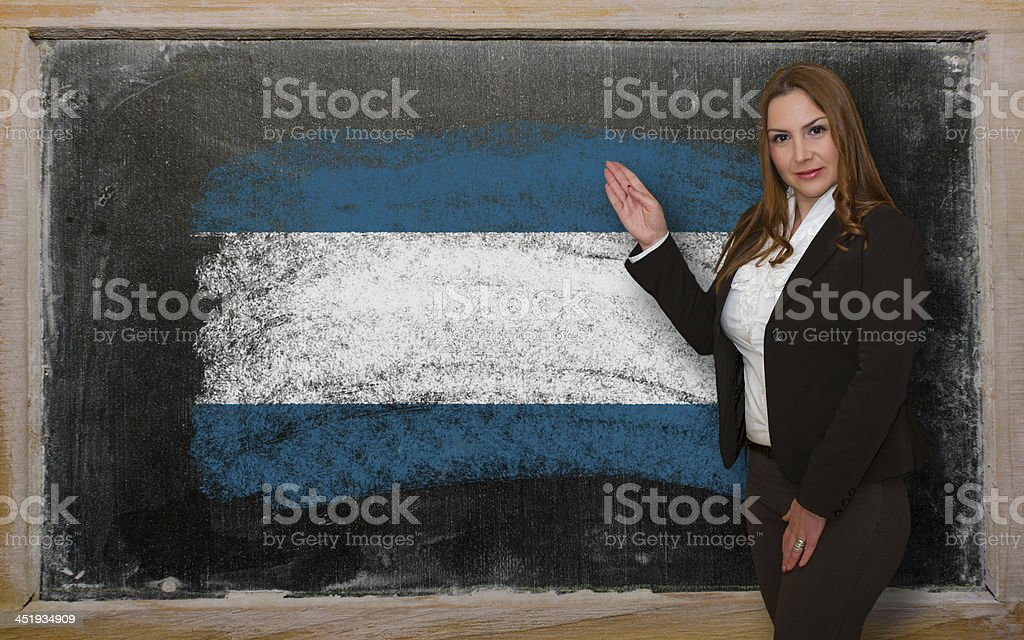 Teacher showing flag of El Salvador on blackboard for presentation stock photo