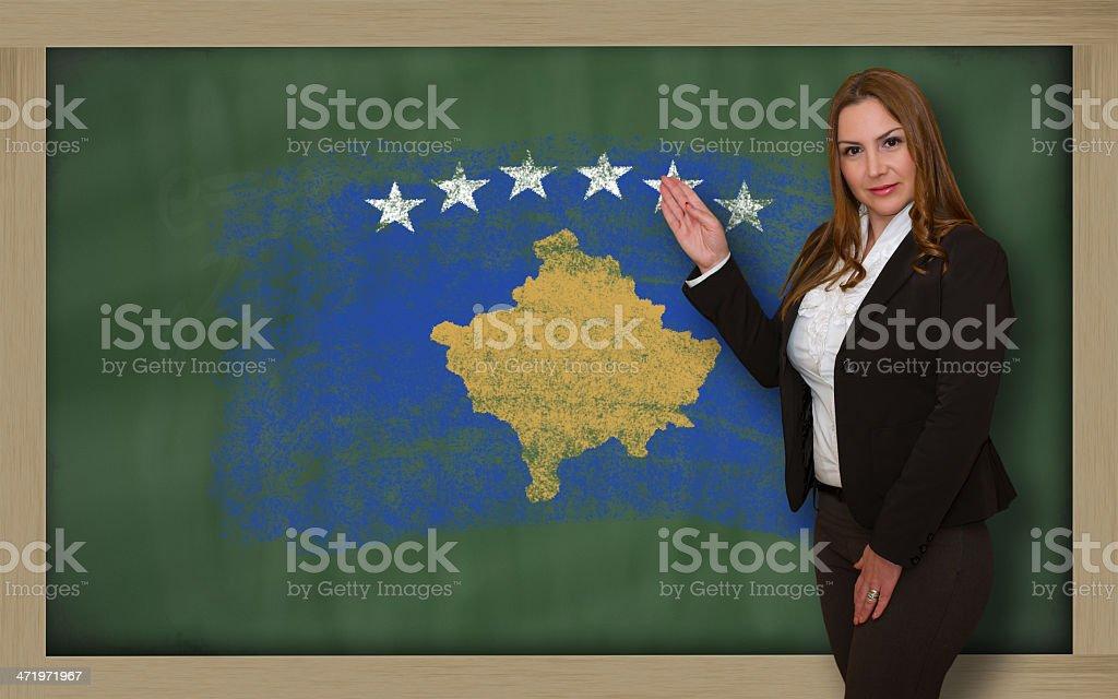 Teacher showing flag of kosovo on blackboard for presentation stock photo