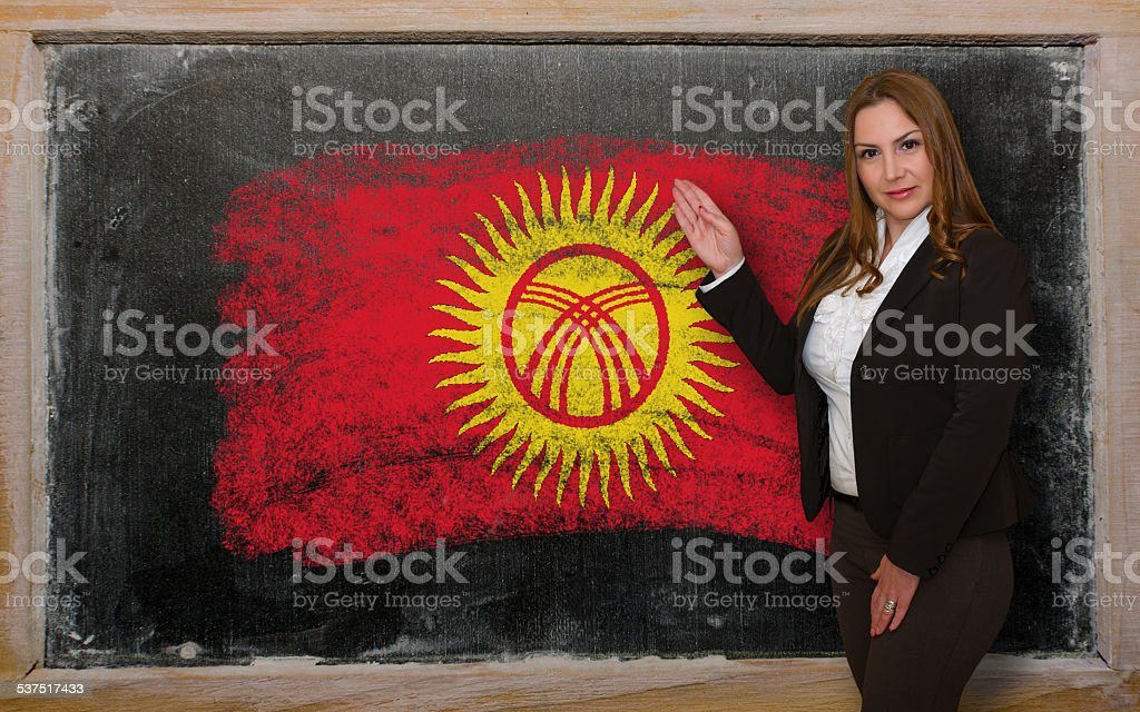 Teacher showing flag of Kyrghyzstan on blackboard for presentation stock photo