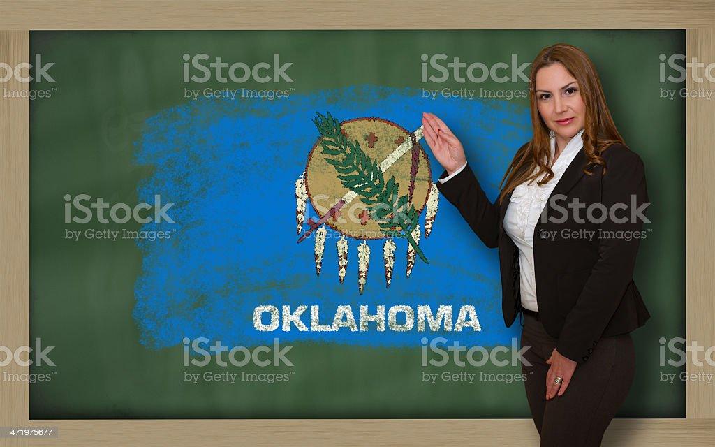 Teacher showing flag of oklahoma on blackboard for presentation royalty-free stock photo