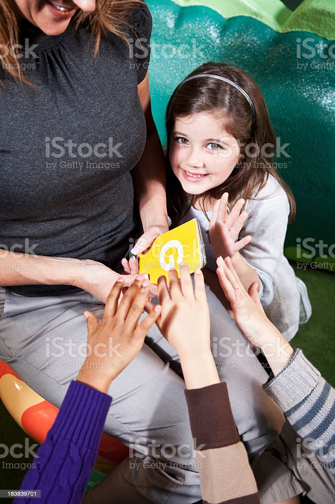 Teacher showing flashcards to group of children stock photo