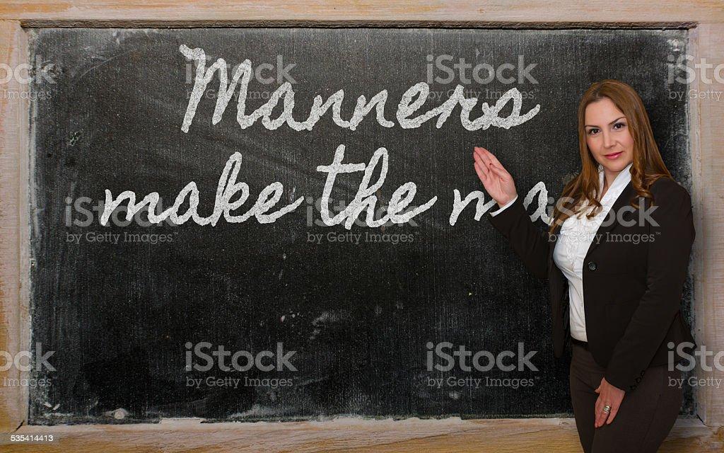 Teacher showing Manners make the man on blackboard stock photo