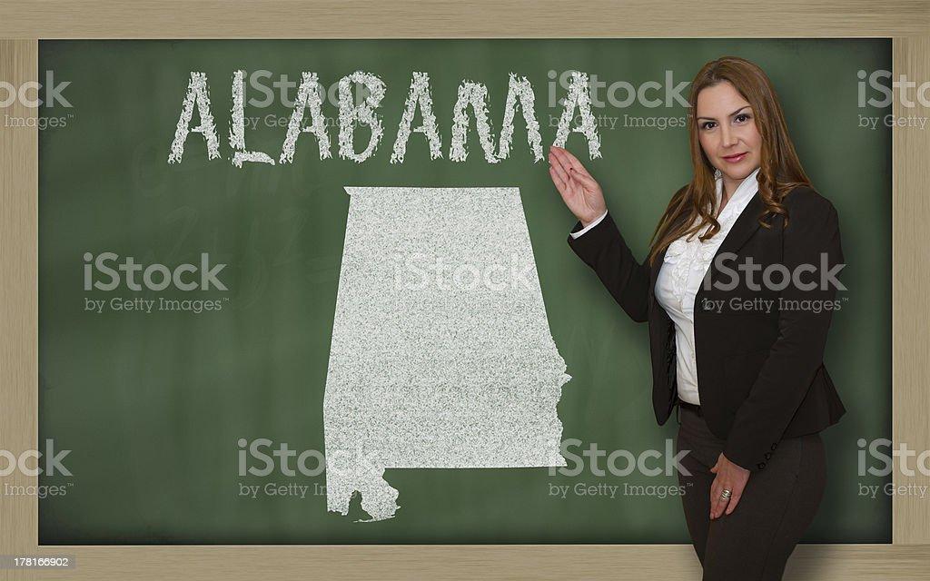 Teacher showing map of alabama on blackboard royalty-free stock photo