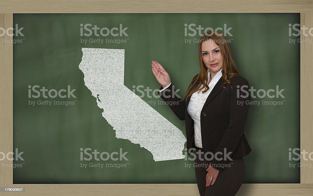 Teacher showing map of california on blackboard royalty-free stock photo