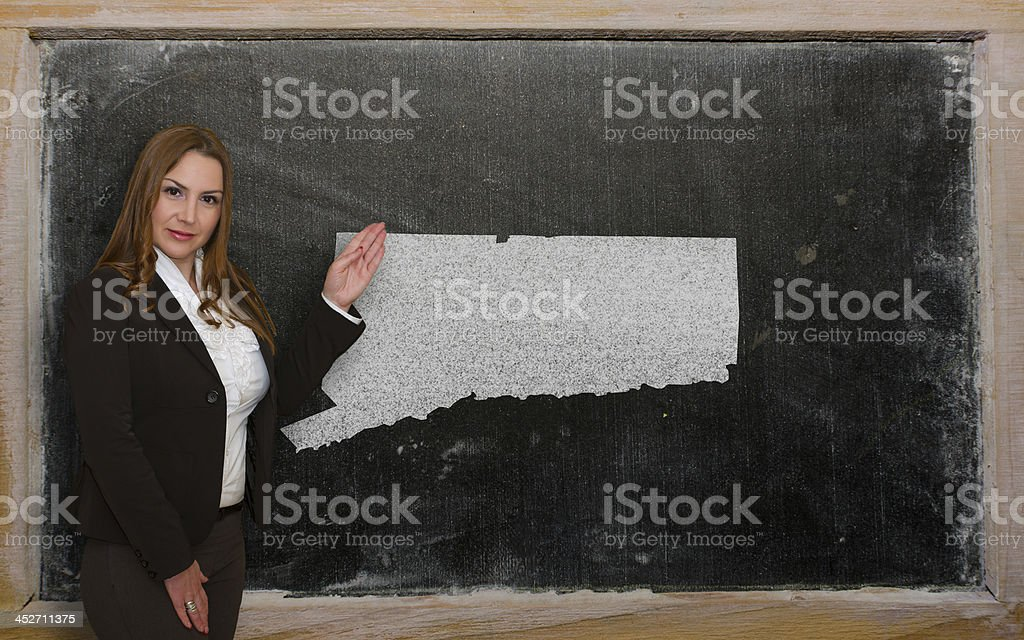 Teacher showing map of connecticut on blackboard stock photo