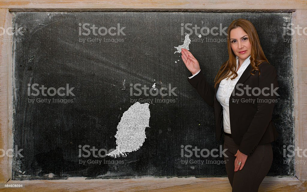 Teacher showing map of grenada on blackboard stock photo
