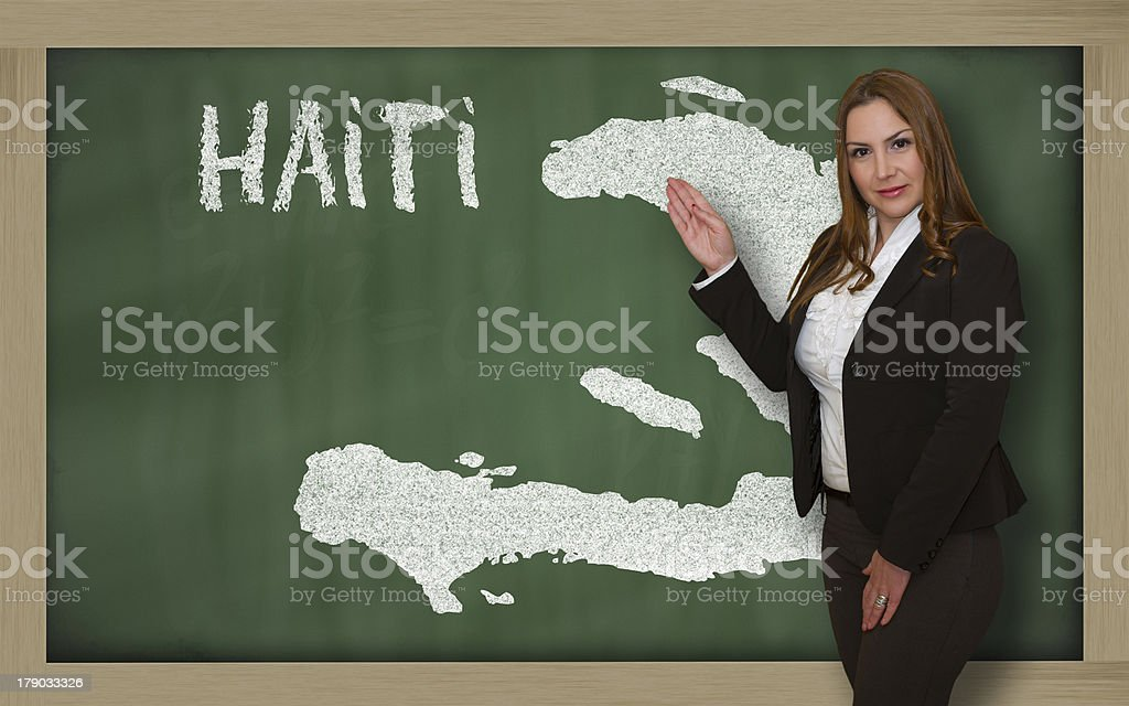 Teacher showing map of haiti on blackboard royalty-free stock photo