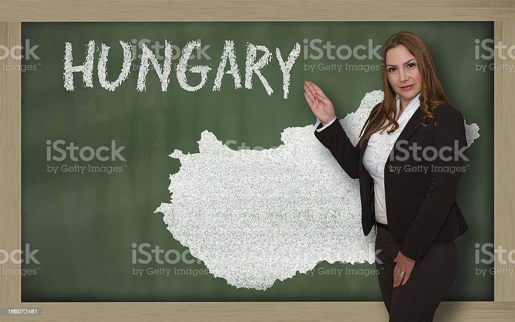 Teacher showing map of hungary on blackboard royalty-free stock photo