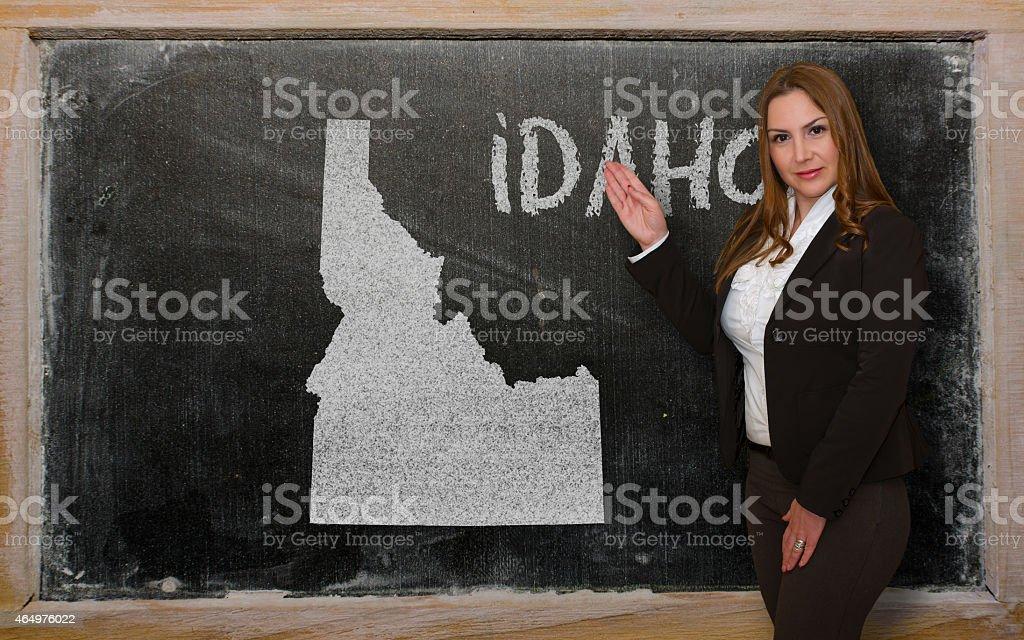 Teacher showing map of idaho on blackboard stock photo