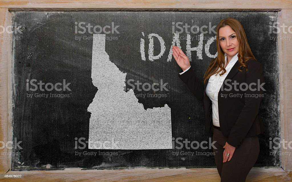Teacher showing map of idaho on blackboard stock photo