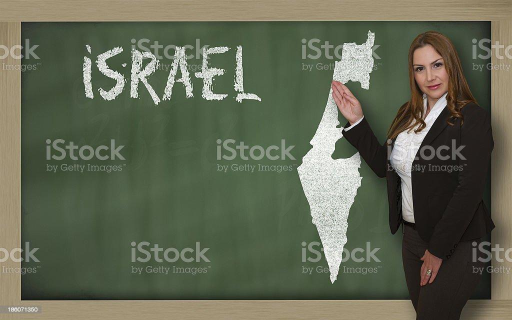 Teacher showing map of israel on blackboard royalty-free stock photo