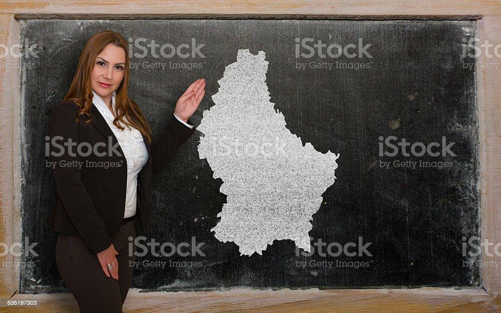 Teacher showing map of luxembourg on blackboard stock photo